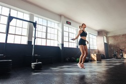 Young woman exercising using skipping rope in gym. Athletic woman training hard at the gym.