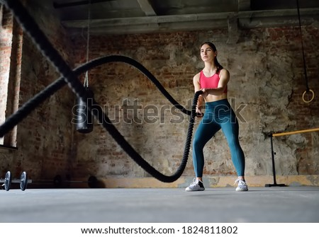 Young woman exercising with battle ropes at the gym. Strong female athlete doing crossfit workout with battle rope. Regular sports boosts immune system and promote good health. Healthy lifestyle