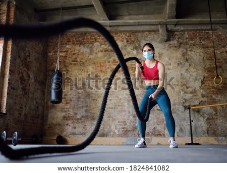 Young woman exercising with battle ropes at the gym. Strong female athlete doing crossfit workout with battle rope during epidemic COVID-19. Woman wearing medical face mask in gym