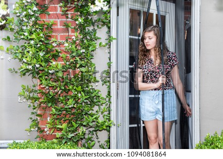 Young woman exiting house entering outdoor spring garden with hanging plant flowers covering brick wall in backyard porch of home by door, insect net #1094081864