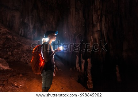 Young woman explores the cave with a torch