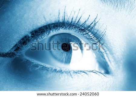 Young woman eye closeup. Soft blue tint.