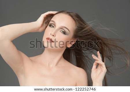 Young woman face with hair motion on gray background isolated close up portrait.