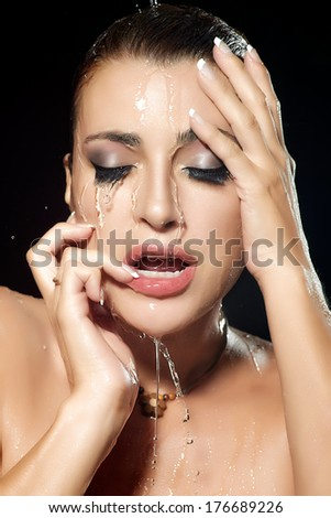 Young woman face with water falling down. Beauty and fashion make-up under flowing water. Closeup portrait isolated on black