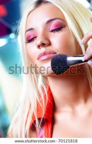 Young woman fashion makeup preparation.