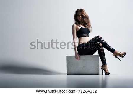 Young woman fashion. On wall background.