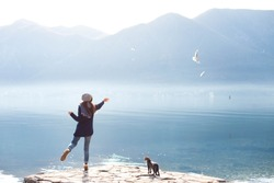 Young woman feeds seagulls and cat at winter sea beach. Amazing coastline scene with girl, animals, mountains, fog, blue water and morning light. Concept of freedom, travel, flying. Lifestyle moment.