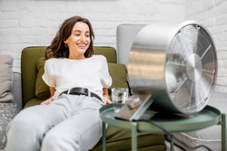Young woman feeling hot, enjoying the flow of air from the fan, sitting on the couch with a glass of water at home. Concept of abnormal summer heat and thirst