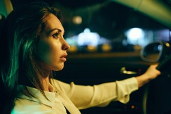 Young woman feeling sad and crying while driving car alone at night.