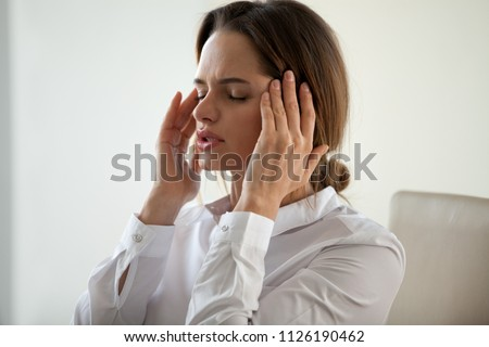 Young woman feeling strong headache attack concept, exhausted tired businesswoman massaging temples to relieve pain feeling migraine, stressed fatigued lady suffering from pain in aching head