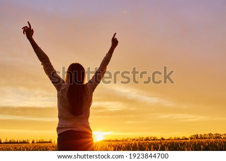 Young woman feeling victorious facing the beautiful sunset. Stock foto ©
