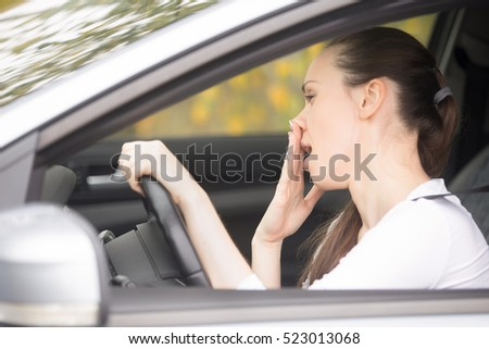 Young woman fell asleep during car ride, can\'t concentrate or feeling ill. Lady driver leaning on steering wheel, suffering whether from alcohol, poor sleep, new medication, or having horrible cold