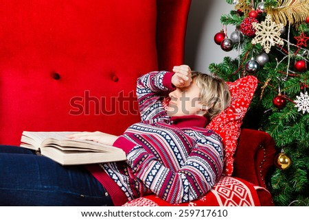young woman fell asleep with a book on a red couch at Christmas tree