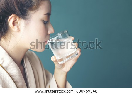 Young woman felling thirsty, drinking cold water after finished from hot sauna session at Spa Center - Spa Concept - Shutterstock ID 600969548