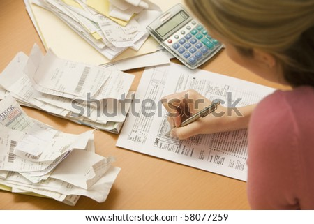 Young woman fills out tax information at her desk with piles of receipts.  Horizontal shot.