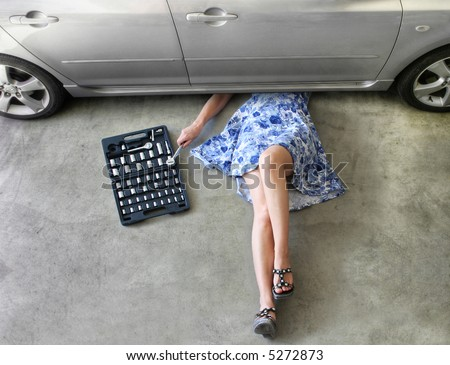 Young woman fixing a car in a garage.