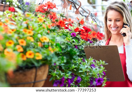 Young woman florist working in the greenhouse.