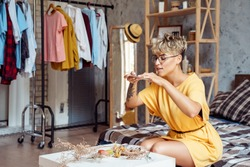 Young woman food blogger wearing eyeglasses sitting at stylish urban apartment taking photo of plate with desserts macaroons and eclairs on smartphone smiling joyful