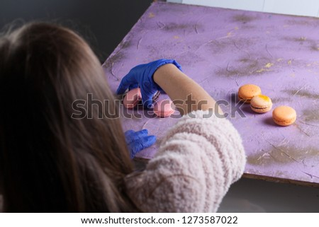 Young woman food photo stylist prepares to photoshoot macaroons on the violet photo backdrop board