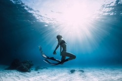 Young woman freediver glides over sandy sea with fins. Freediving in blue ocean and sun light