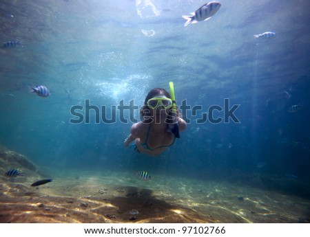 Young woman freediving in a clear tropical sea with sandy bottom among fish