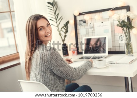 Young woman freelancer indoors home office concept winter atmosphere sitting writing in planner smiling