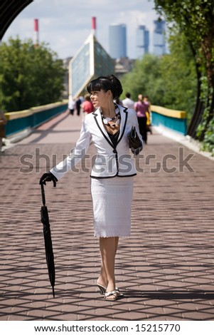 Young woman from high society walking at sunny day in city.