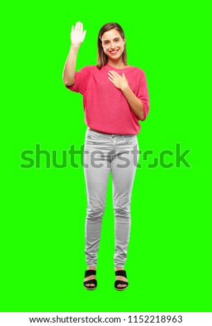 young woman full body. smiling confidently while making a sincere promise or oath, solemnly swearing with one hand over heart.