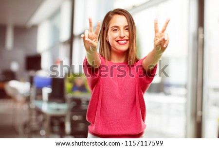 young woman full body. with a proud, happy and confident expression; smiling and showing off success while gesturing victory with both hands, giving an