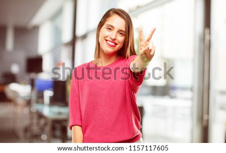 young woman full body. with a proud, happy and confident expression; smiling and showing off success while gesturing victory, giving an