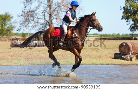 Young woman gallops a horse through water