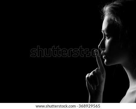 Young Woman Gesturing For Being Quiet, Shows Silence Sign In Dark Background With Copyspace, monochrome image