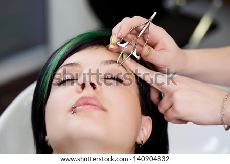 young woman gets her eyebrows plucked in salon