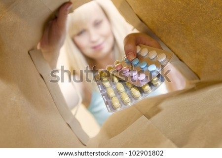 young woman gets of many different pills from a package