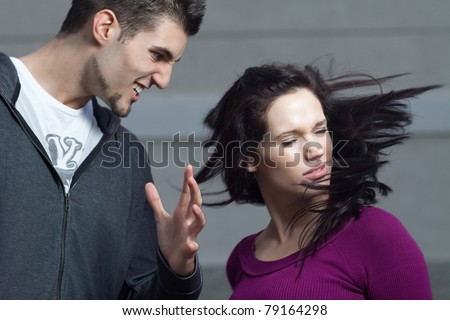 Young woman gets slapped by her boyfriend. Action shot with selective focus on her face. Shallow depth of field.