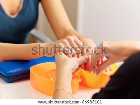 Young woman getting a manicure in a nail salon.