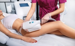 Young woman getting cryolipolyse treatment in cosmetic cabinet. Cool sculpting procedure for slimming thighs. Body Fat freezing technology