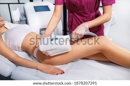 Young woman getting cryolipolyse treatment in cosmetic cabinet. Cool sculpting procedure for slimming thighs. Body Fat freezing technology Stockfoto ©