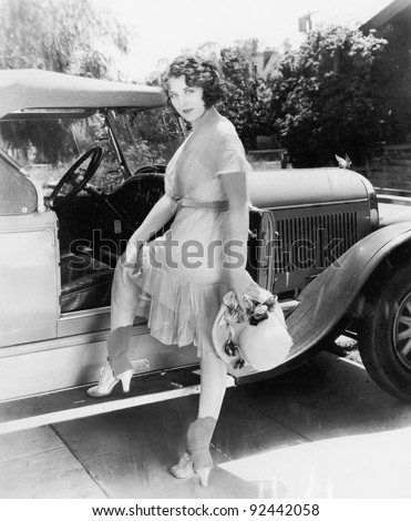 Young woman getting into her car for a drive in the country