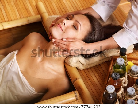 Young woman getting massage in bamboo spa
