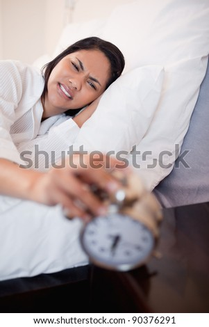 Young woman getting pain in the ears by alarm clock