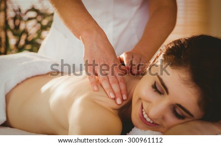 Young woman getting shoulder massage in therapy room