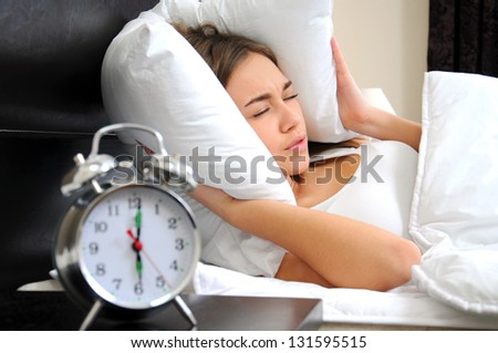 Young woman getting stressed about waking up too early