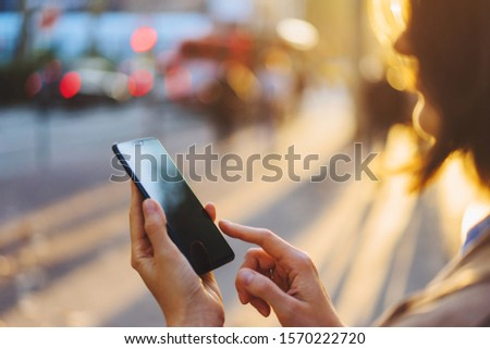 Young woman getting taxi via cab application on smartphone while standing on city street at evening. Woman texting message in chat on mobile phone walking outdoors. 4G internet