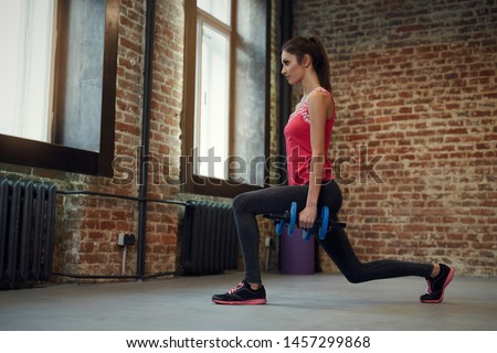 Young  woman/girl doing  exercise with dumbbells. Fit female   training in the health club.
