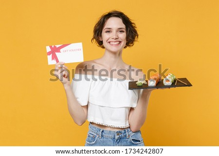 Young woman girl in casual clothes hold in hand gift certificate makizushi sushi roll served on plate traditional japanese food isolated on yellow background studio portrait. People lifestyle concept. Stock photo ©