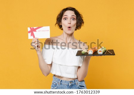 Young woman girl in casual clothes hold in hand gift certificate makizushi sushi roll served on plate traditional japanese food isolated on yellow background studio portrait. People lifestyle concept. Stok fotoğraf ©