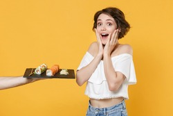 Young woman girl in casual clothes hold in hand gives takes makizushi sushi roll served on black plate traditional japanese food isolated on yellow background studio portrait People lifestyle concept
