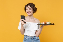 Young woman girl in casual clothes hold in hand makizushi sushi roll served on black plate japanese food using mobile cell phone isolated on yellow background studio portrait People lifestyle concept