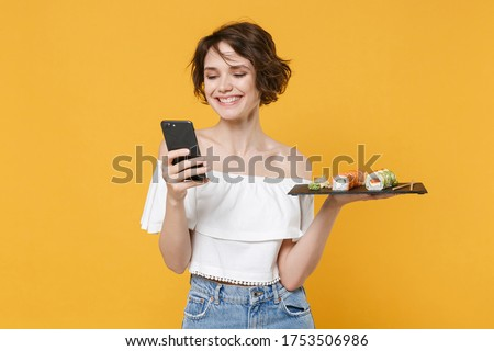 Young woman girl in casual clothes hold in hand makizushi sushi roll served on black plate japanese food using mobile cell phone isolated on yellow background studio portrait People lifestyle concept Stok fotoğraf ©